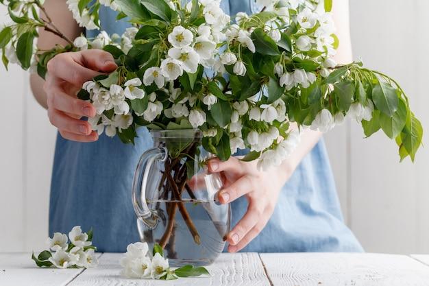 Boeket van lentebloemen in de handen van een meisje op een achtergrond van blauwe jurk. bloeiende appelboom in het voorjaar