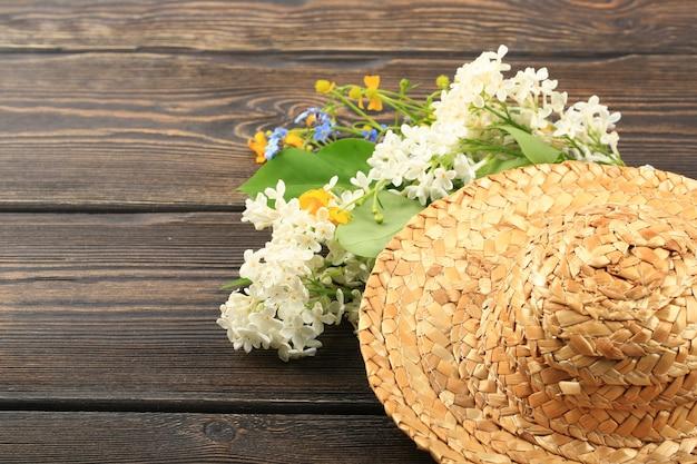Boeket van lentebloemen in een strohoed op een houten ondergrond