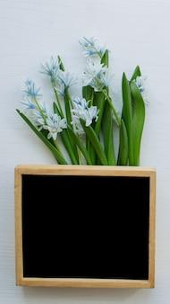 Boeket van lentebloemen naast houten frame met zwarte muur. kopieer ruimte. bovenaanzicht.