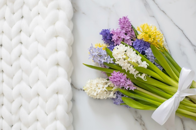 Boeket van lentekleurige bloemen van hyacinten wit marmer en fluffy gebreide plaid