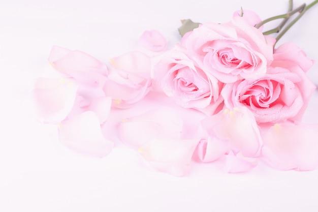 Boeket van lichtroze rozen met bloemblaadjes op een lichte achtergrond