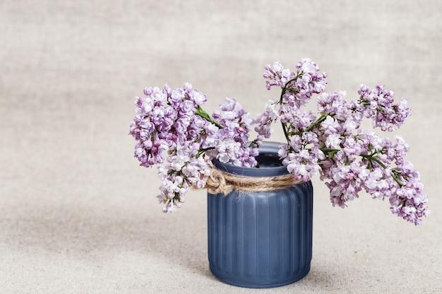Boeket van lila bloemen in blauwe glazen vaas op wazig