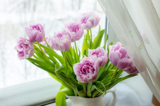 Boeket van lila tulpen in een vaas voor het raam