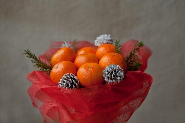 Boeket van mandarijnen en kerstboomtakken. eetbaar nieuwjaarsboeket van fruit. cadeau voor kerstmis. doe-het-zelf cadeau. nuttig geschenk gemaakt van fruit. decoratie van kegels en mandarijnvruchten.