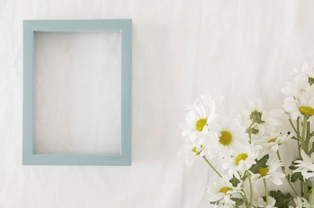 Boeket van mooie bloemen op groene stelen in de buurt van frame