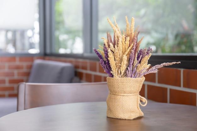 Boeket van mooie droge planten in een moderne vaas op houten tafel voor huisdecoratie