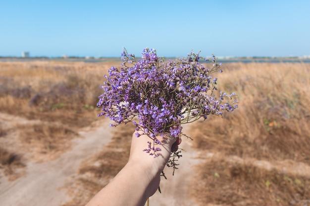 Boeket van mooie paarse bloemen in de hand van de vrouw