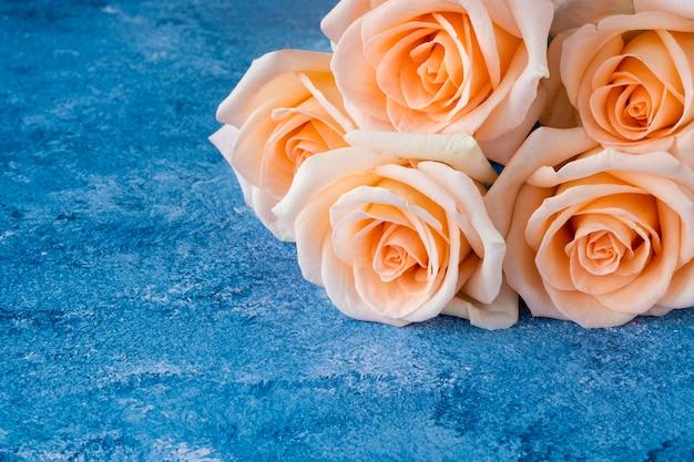 Boeket van mooie perzikkleurige rozen op een blauwe en witte acrylverf