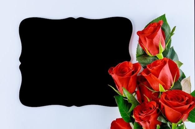 Boeket van mooie rode rozen met mockup zwarte bord geïsoleerd op een witte achtergrond. moederdag of valentijnsdag.