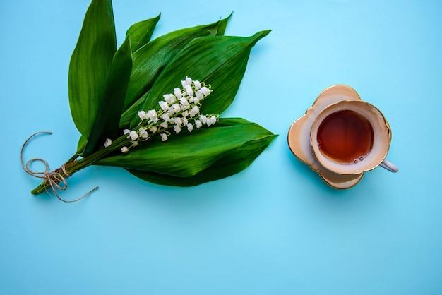 Boeket van mooie witte lelies van de vallei met groene bladeren en thee in een kopje op blauw