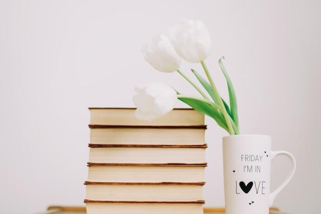 Boeket van mooie witte tulpen. verse lentebloemen en boeken op witte achtergrond. valentijn en 8 maart concept