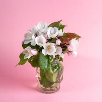 Boeket van natte bloeiende roze appelboom twijgen in glas kan op roze achtergrond. moederdag, valentijnsdag, verjaardag gefeliciteerd concept. wenskaart.