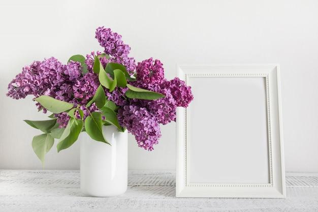 Boeket van paarse lila bloemen en witte fotolijst op licht bord.