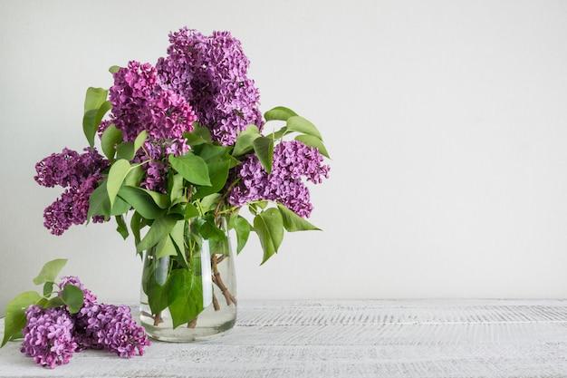 Boeket van paarse lila bloemen in glazen vaas in witte interieur. ruimte voor tekst.