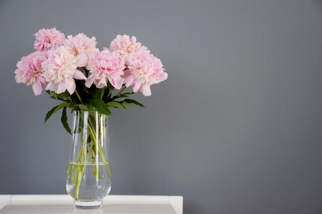 Boeket van pastel roze pioen bloemen in bloei in glazen vaas op witte tafel op grijze muur achtergrond