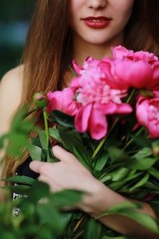 Boeket van peony. mooie jonge vrouw ligt tussen pioenrozen. feestdagen en evenementen. valentijnsdag. lente bloesem.
