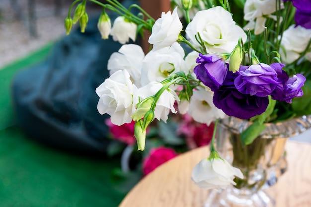 Boeket van pioenroos witte rozen in een vaas op een tafel in een café
