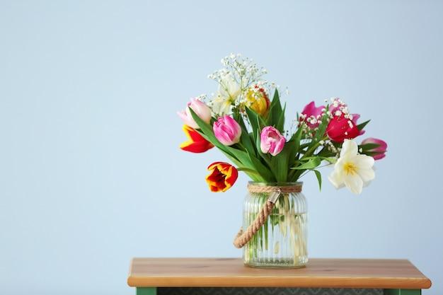 Boeket van prachtige kleurrijke tulpen op houten tafel tegen lichtblauwe muur