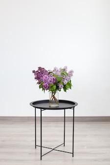 Boeket van prachtige lila lentebloemen in vaas op zwarte vintage salontafel, woondecoratie. interieur ontwerp.