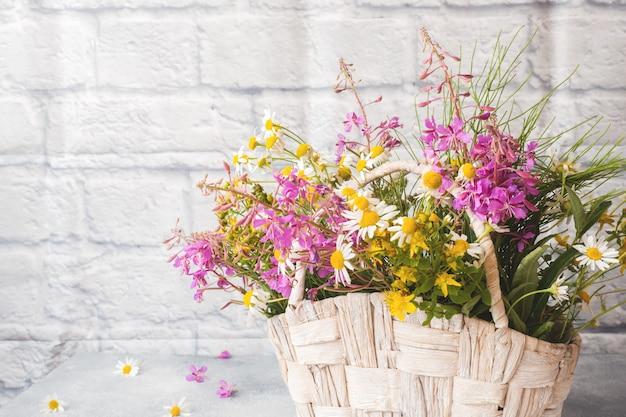 Boeket van prachtige wilde bloemen in een mand op een grijze achtergrond met kopie ruimte.