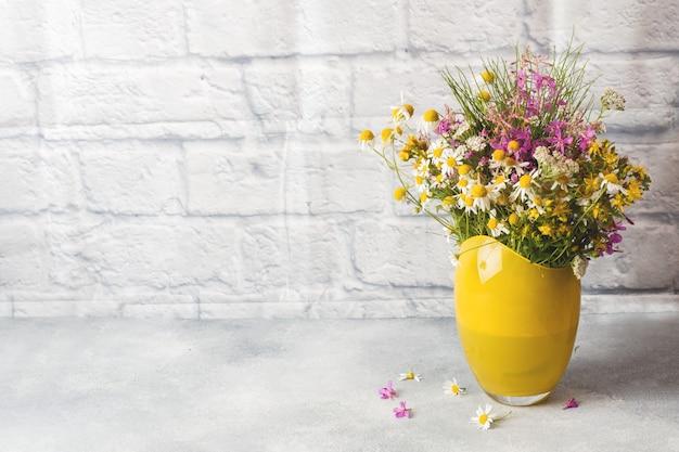 Boeket van prachtige wilde bloemen in vaas op een grijze ondergrond met kopie ruimte.
