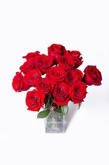 Boeket van rode (bourgondië) rozen op een witte achtergrond. waterdruppels. detailopname.