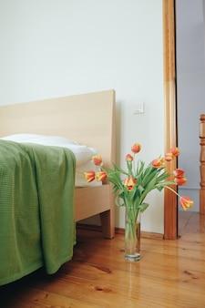 Boeket van rode gele tulpen in een slaapkamer op de achtergrond van het bed. liefde concept