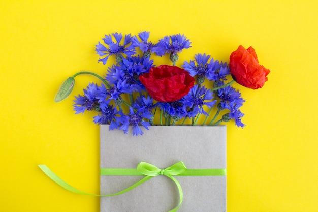 Boeket van rode papavers en blauwe korenbloemen in een gebonden envelop