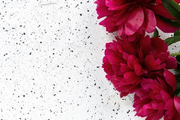 Boeket van rode pioen bloemen op een witte cement tafel. vakantie concept, 8 maart, moederdag. bovenaanzicht, plaats voor tekst
