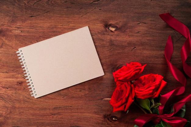 Boeket van rode rozen en een lege blocnote op een gestructureerde houten achtergrond