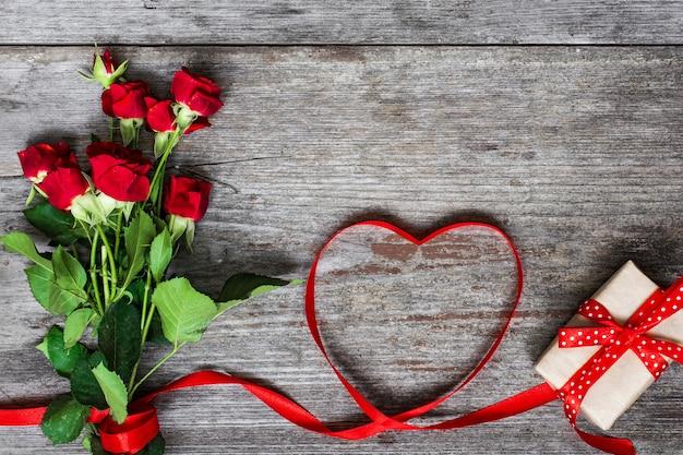 Boeket van rode rozen en hartvormig rood lint
