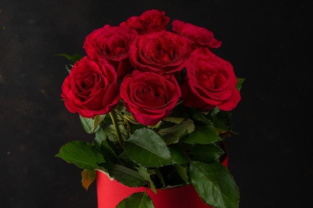 Boeket van rode rozen in rode pot op donkere achtergrond.