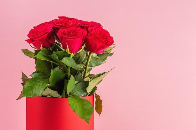 Boeket van rode rozen in rode pot op roze achtergrond.