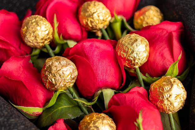 Boeket van rode rozen met gouden chocolade