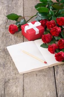 Boeket van rode rozen, notebook en geschenkdoos