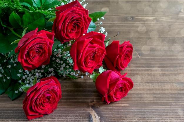 Boeket van rode rozen op de houten tafel in sunlights onder een hoek. leuk cadeau voor groet met valentijnsdag