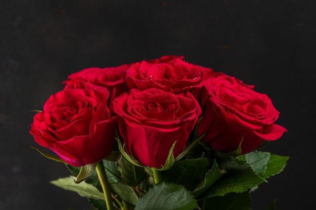 Boeket van rode rozen op donkere achtergrond.