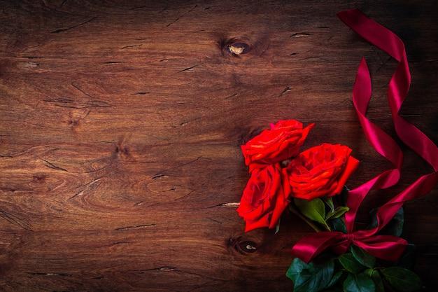 Boeket van rode rozen op een gestructureerde houten achtergrond, vrije ruimte voor tekst