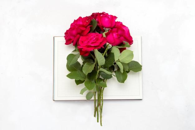 Boeket van rode rozen op een open dagboek op een lichte stenen achtergrond. plat lag, bovenaanzicht