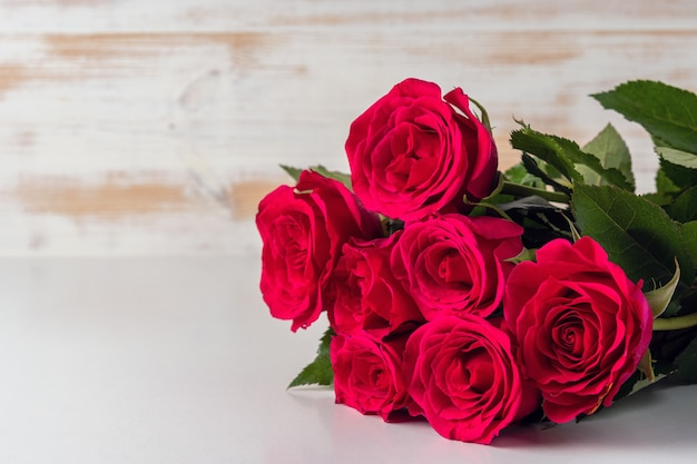 Boeket van rode rozen op houten tafel.