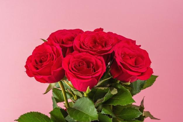 Boeket van rode rozen op roze achtergrond.