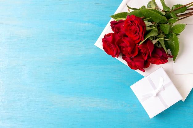 Boeket van rode rozen, witte geschenkdoos, blauwe houten achtergrond. kopieer ruimte. romantisch cadeau voor valentijnsdag vakantie