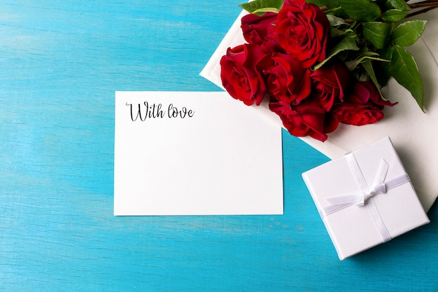 Boeket van rode rozen witte geschenkdoos schoon blad, blauwe houten achtergrond. kopieer ruimte. romantisch cadeau voor de valentijnsdag vakantie. verjaardag. plat lag, bovenaanzicht