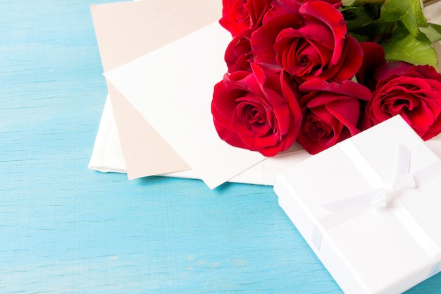 Boeket van rode rozen witte geschenkdoos schoon blad, blauwe houten achtergrond. kopieer ruimte. romantisch cadeau voor valentijnsdag vakantie