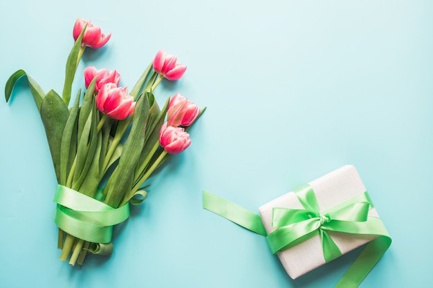 Boeket van rode tulp en geschenkdoos op blauw.