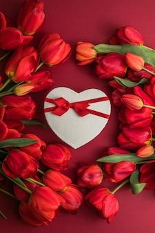 Boeket van rode tulpen en geschenkhartdoos, arrangement met veel kopieerruimte voor tekst