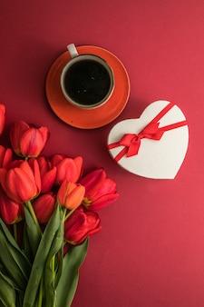 Boeket van rode tulpen en geschenkhartdoos, koffiekoparrangement met veel kopieerruimte voor tekst
