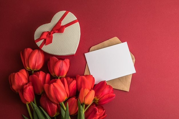 Boeket van rode tulpen en hart geschenkdoos geïsoleerd op rode ondergrond