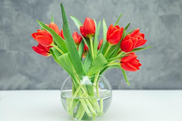 Boeket van rode tulpen in een vaas op een grijze tafel. feestelijke stemming van de lente.