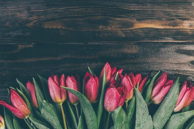 Boeket van rode tulpen op een houten tafel in een donkere stijl